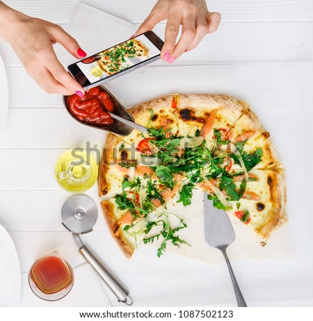 Girl takes pictures of seafood pizza and sauces on white wood table