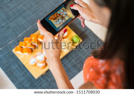 Girl takes pictures of sushi on phone. A girl takes pictures of sushi on the phone that lie on a black table