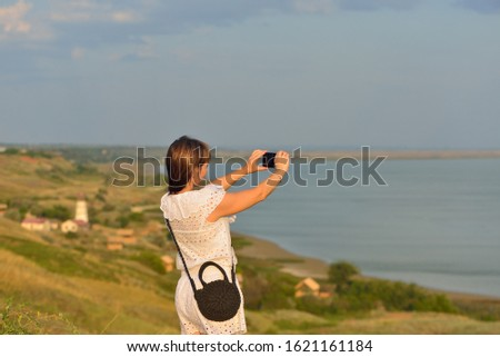 girl takes pictures of the seascape on the phone