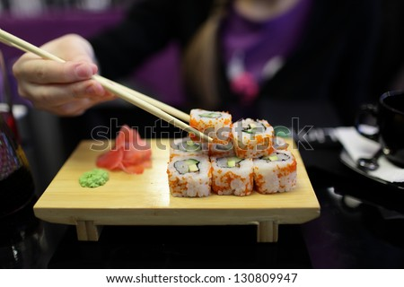 Girl takes sushi in the japanese restaurant