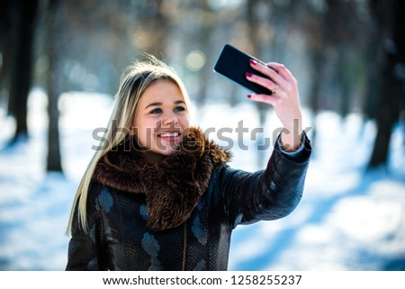 Girl taking a selfie at the park #1258255237