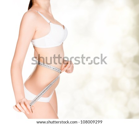 girl taking measurements of her body, golden blurred background with a space for your message or graphics