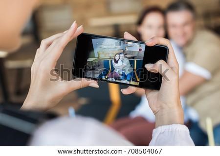 girl taking photo of taking photo of mature couple