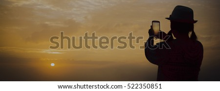 Girl taking photo with mobile phone in morning night sunrise on mountain fog sea