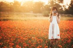 Girl taking picture on poppy field