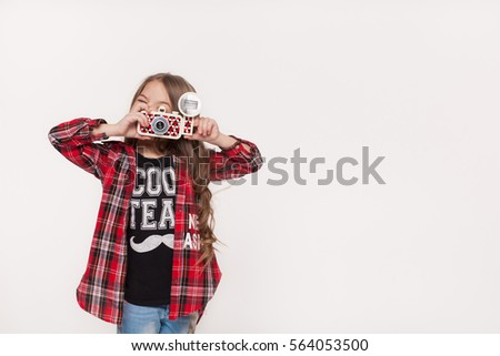 Girl taking picture with a retro camera isolated on white