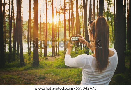 Girl taking pictures in forest