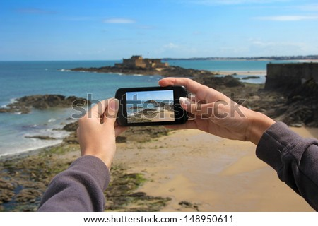 Girl taking pictures on a mobile phone in the Fort on island Petit Be in Saint-Malo