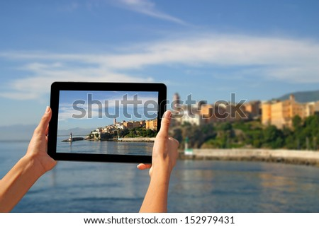 Girl taking pictures on a tablet in Bastia, Corsica, France. - stock photo