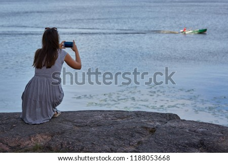 Girl taking pictures on mobile phone motor boat