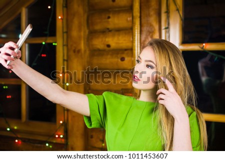 Girl taking selfie wearing green dress in a log cabin