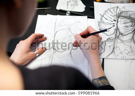 Girl tattoo artist draws a sketch with a sheet of Monstera. Close-up of hand drawing with a creative workplace #599081966