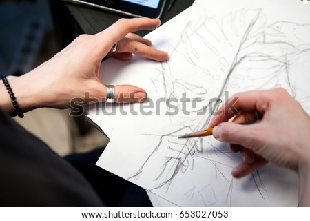 Girl tattoo artist draws a sketch with a sheet of Monstera. Close-up of hand drawing with a creative workplace #653027053
