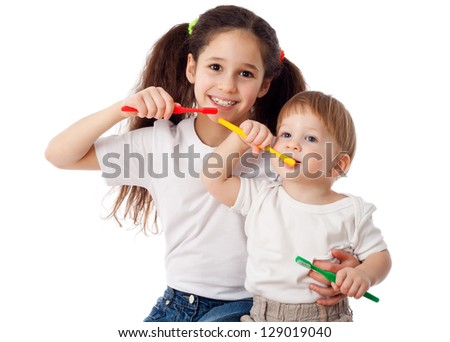 Girl teaches little boy brushing teeth, isolated on white