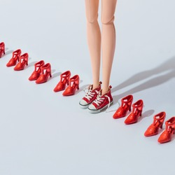 Girl teen doll in red sneakers with fashion high heels shoes. Minimal lifestyle concept.