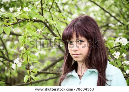 girl  teenager against a blossoming pear in the spring afternoon - stock photo