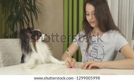Girl teenager and dog Papillon guess on desires, writes desire to pieces of paper #1299005998