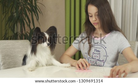 Girl teenager and dog Papillon guess on desires, writes desire to pieces of paper #1309691314