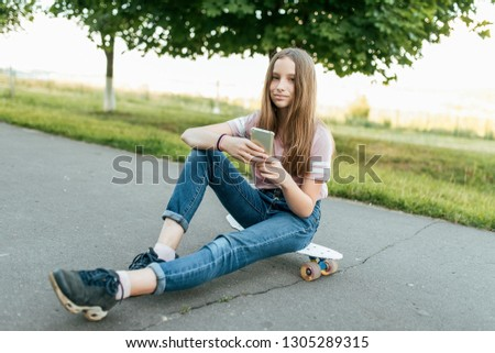 Girl teenager 10-12 years old, sits on board in hands of phone. In summer in city in casual jeans and a pink T-shirt. Communication in the Internet, in hands of holding a smartphone. Smiles and poses. Stockfoto ©