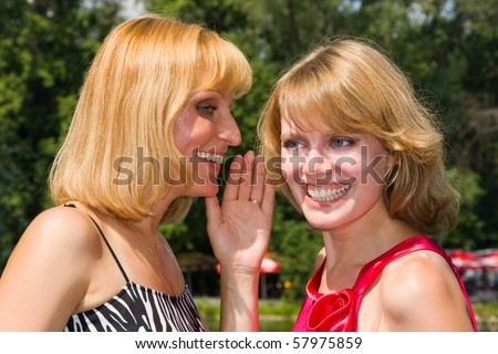 Girl telling a secret to another gossip. Two happy women sharing funny gossip. Gossip - two beautiful girls.  Happy young women friends talking and laughing.  Woman i is telling a secret to another.