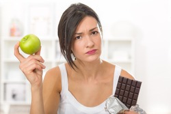 Girl tempted to eat a chocolate instead of an apple after work out