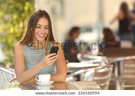 Girl texting on the smart phone in a restaurant terrace with an unfocused background #226560994