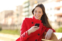 Girl texting on the smart phone sitting in a park wearing a red jacket and sitting in a bench in a park
