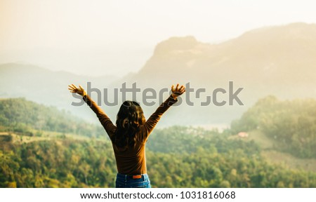 Girl thank for giving.raised hands at mountains.Travel with nature landscape #1031816068