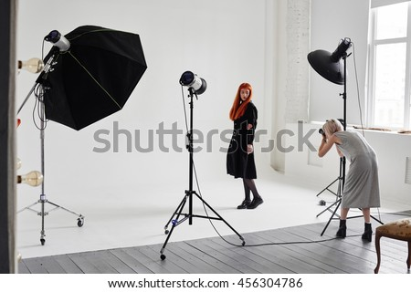 Girl the photographer takes pictures of model in black on a white background in Studio