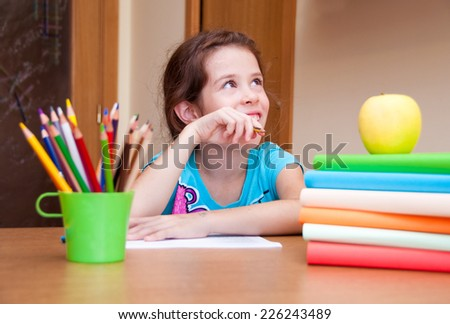 Girl thinking and writing on desk