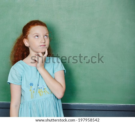 Girl thinking at chalkboard in elementary school class