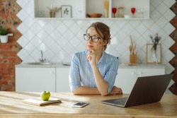 Girl thinking working with laptop at home. Self-isolation, working from home.