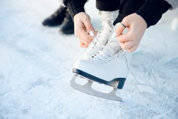 Girl ties shoelaces on white figure skates for ice rink in winter. Christmas holidays concept.