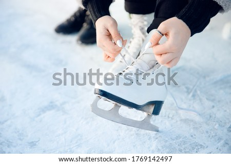 Photo of  Girl ties shoelaces on white figure skates for ice rink in winter. Christmas holidays concept.