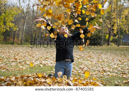 Girl tossing colorful fall leaves into the air - stock photo