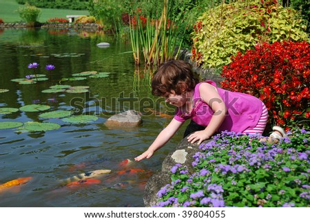 Girl touching big colorful fishes in a pond