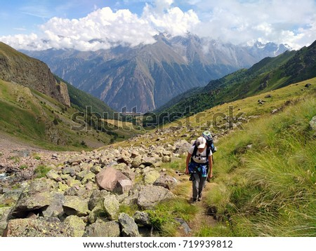 Girl tourist on a mountain trail hiking, walking along the trail, rising between steep slopes #719939812