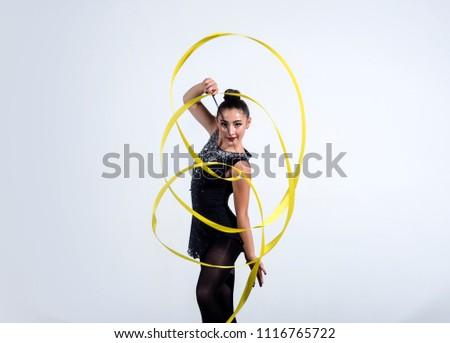 girl train acrobatics with ribbon. girl curl yellow ribbon in rhythmic gymnastics