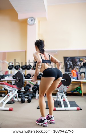 Girl training by the barbell