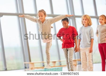 Girl trains balance on balance beam in elementary school physical education
