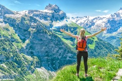 girl traveler, arms outstretched, against the backdrop of mountain peaks, the Engelberg, Switzerland