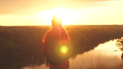Girl traveler in the rays of the sunset sun with a backpack. Young woman tourist walks on a high mountain meeting the sunrise. Thirst for adventure in finding yourself. Research findings of various