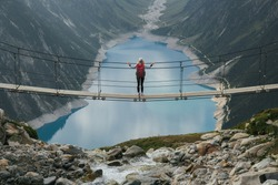 Girl traveler with a backpack in the mountains. A young girl stands on a suspension bridge on a background of mountains and glaciers. Travel and active life concept. Adventure trip to Europe.