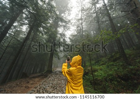 Girl traveller wearing yellow jacket and taking picture on her phone. Autumn and raining season with dark green tones while a girl in yellow rain jacket walks in the forest,  fog, rain and clouds