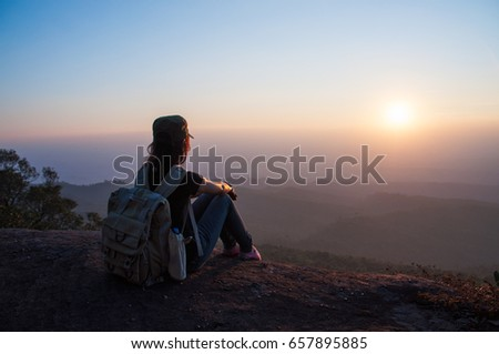 Girl travels at mountains alone relaxing with beautiful sunset sky view, Travel lifestyle hiking concept , vacation outdoor concept - Shutterstock ID 657895885