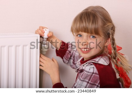 Girl try open thermostat. Energy crisis.