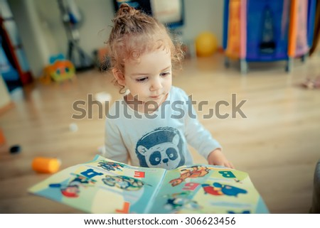 girl trying to read a children\'s book