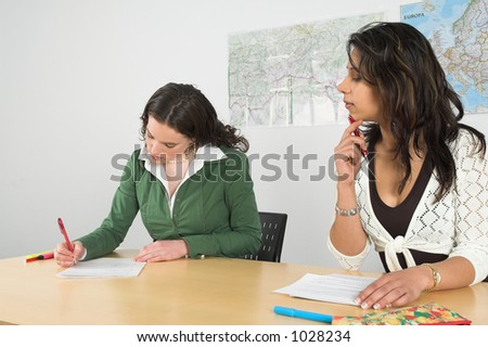 Girl trying to take a peek at what her friend is writing on her exam paper