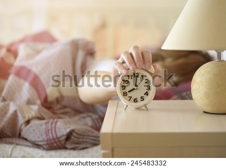 girl turns off the alarm clock waking up in the morning from a call