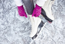 Girl tying shoelaces on ice skates before skating on the ice rink, hands in purple or pink knitted gloves.